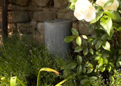 Beton Cylinder Lautsprecher der Größe medium im Beet mit Lavendel und weißen Rosen.