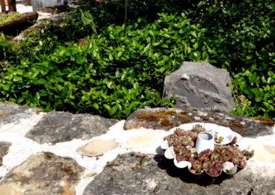 Vinca minor, die mit den kleinen Blättern, umrahmt einen Sonance Rock Lautsprecher.